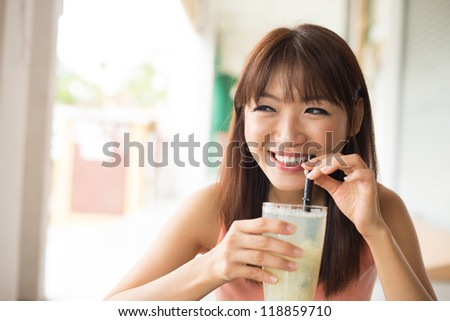 Beautiful Asian woman drinking beverage in the morning sitting outside. - stock photo