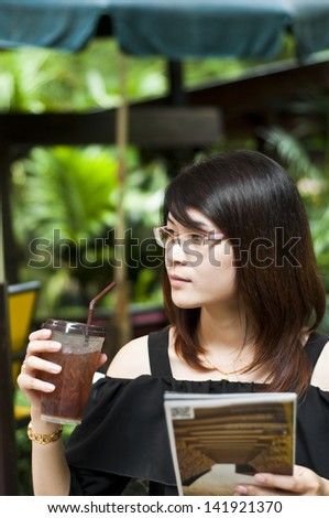 Beautiful Asian woman enjoy iced tea and holding travel guide map. - stock photo