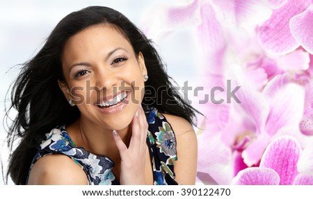 Beautiful Asian woman face over floral background. - stock photo