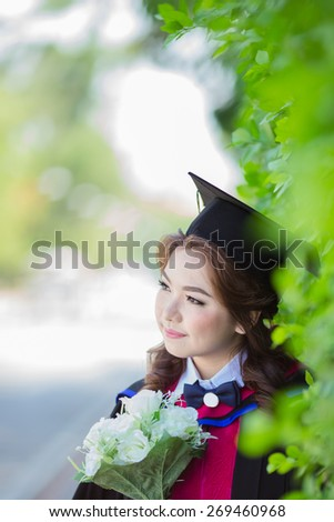 Beautiful asian woman graduating holding flower and smiling - stock photo