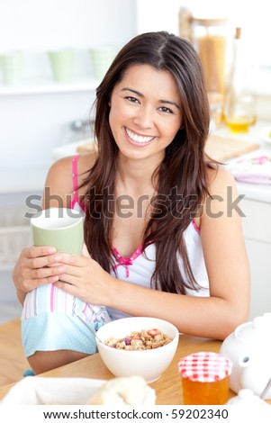Beautiful asian woman having breakfast smiling at the camera sitting in the kitchen - stock photo