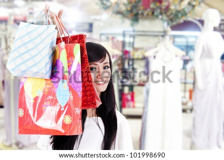 Beautiful Asian woman hides behind her shopping bags shot in shopping mall - stock photo