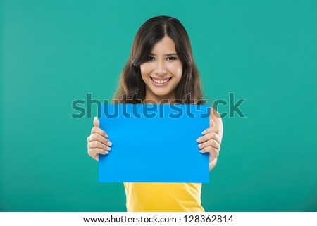 Beautiful asian woman holding a blue billboard, over a green background - stock photo