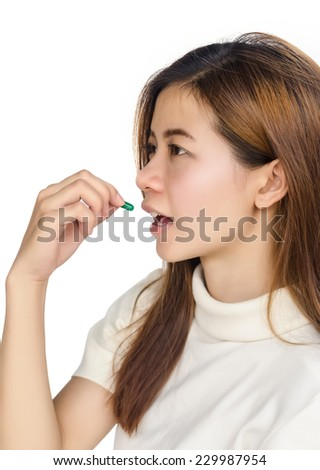 Beautiful asian woman holding a pill against white background. - stock photo