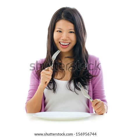 Beautiful Asian woman holding fork and knife with an empty plate ready for food, isolated on white background - stock photo