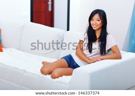 Beautiful asian woman in casual clothings sitting on the sofa at home