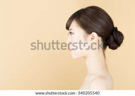 Beautiful asian woman isolated on beige background - stock photo
