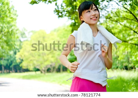 beautiful asian woman jogging in the park - stock photo