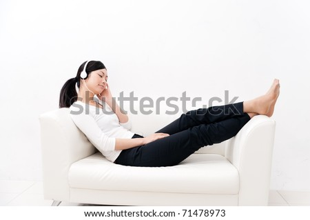beautiful asian woman listening music on the couch - stock photo