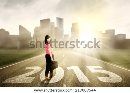 Beautiful asian woman looking at camera while walking on the path to the future 2015 - stock photo