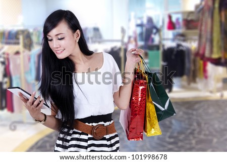 Beautiful asian woman looking at her computer tablet while carrying gift bags