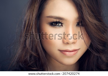Beautiful Asian woman looking directly at camera - hair is covering one half of her face. - stock photo