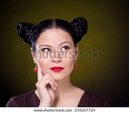 Beautiful asian woman looking for ideas on dark background - stock photo