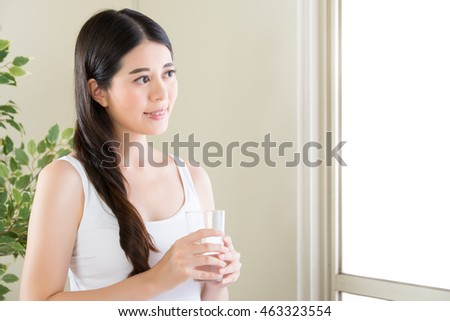 Beautiful asian woman looking out of window and drinking water indoor