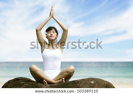 Beautiful asian woman meditating at beach - stock photo