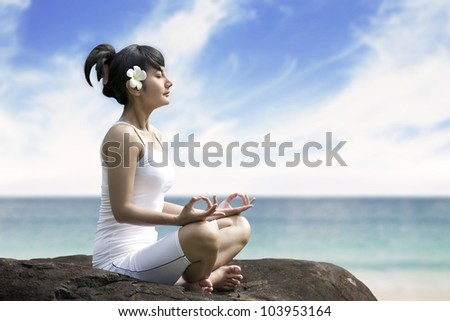 Beautiful asian woman meditating on the beach sitting over a rock - stock photo