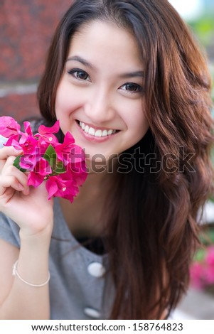 Beautiful asian woman portrait with a pink flower