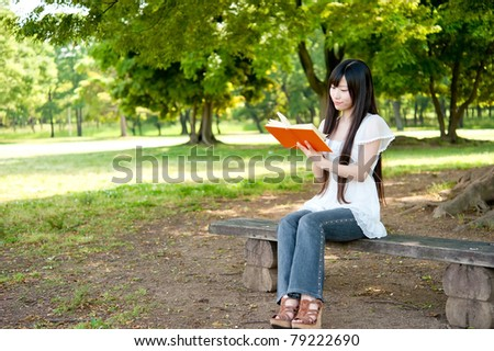 beautiful asian woman reading a book - stock photo