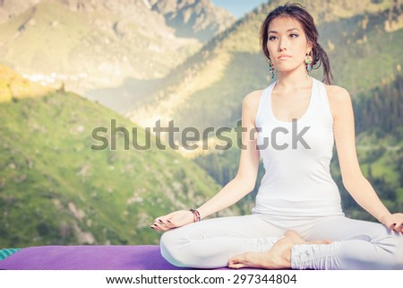 Beautiful asian woman relaxing and meditating outdoor at mountain. She sits at peak of mountain in lotus position and feel harmony of your body and nature. Healthy lifestyles concept of body and soul
