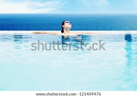 Beautiful Asian woman relaxing in swimming pool