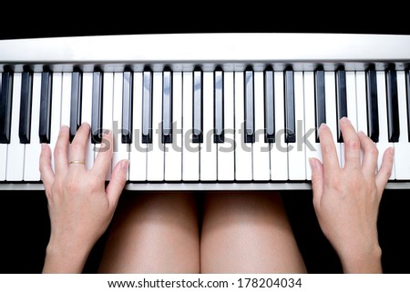 Beautiful Asian woman's hands playing on piano