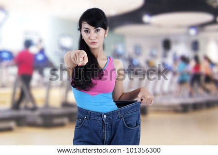 Beautiful Asian woman shows her old huge pair of jeans while pointing to people at front of her, shot in fitness center - stock photo