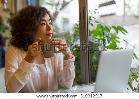 Beautiful asian woman sitting in a cafe with a Cup of coffee and a laptop.