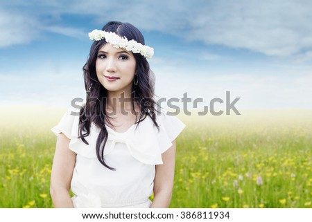 Beautiful Asian woman standing on the meadow with flower crown on her head, smiling at the camera