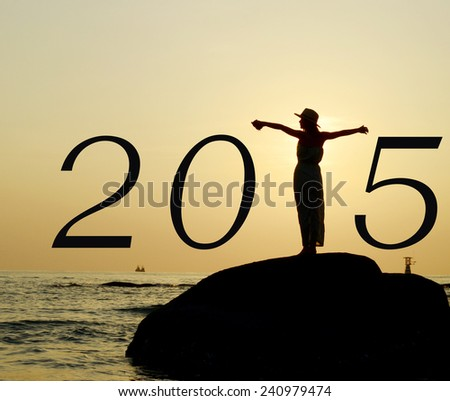 Beautiful asian woman standing, stretching hands, on stone silhouetted the sunrise in morning scene with year 2015 calendar. - stock photo