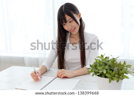 beautiful asian woman studying in the white room - stock photo