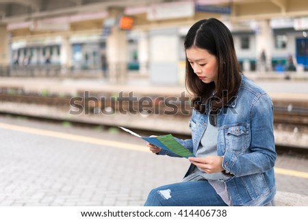 Beautiful asian woman studying map at train station, with copy space