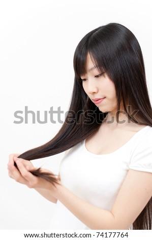 beautiful asian woman taking care of long straight hair - stock photo