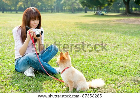 beautiful asian woman taking dog's photo in the park - stock photo