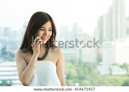 Beautiful asian woman talking on the phone.