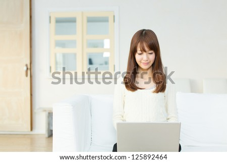 Beautiful asian woman using a laptop computer - stock photo