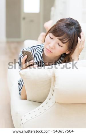 Beautiful asian woman using cellphone - stock photo