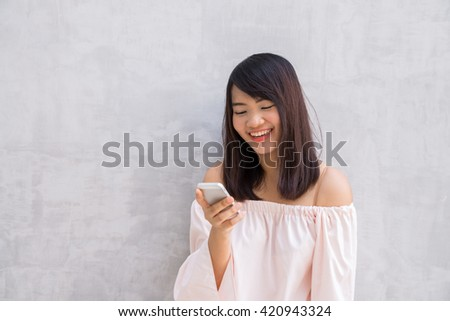 beautiful asian woman using cellphone, over concrete wall - stock photo