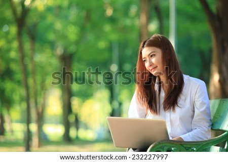 beautiful asian woman using laptop computer in the park