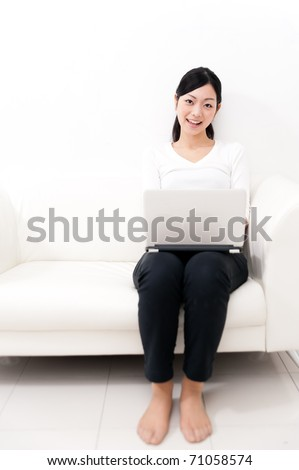 beautiful asian woman using laptop computer on the sofa