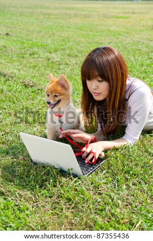 beautiful asian woman using laptop computer with dong in the park