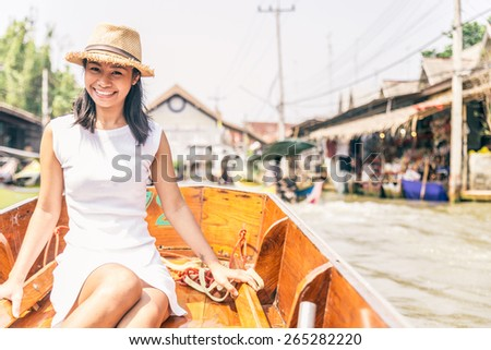 Beautiful asian woman visiting the Floating Market in Bangkok on a boat tour - Asian tourist smiling and looking at camera on a typical thai boat - stock photo