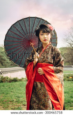 Beautiful asian woman walking in the garden and wearing traditional japanese kimono and traditional umbrella - stock photo