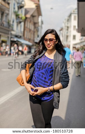 Beautiful Asian Woman Wearing Dress and Glasses Along the Street in Sunny Day   - stock photo