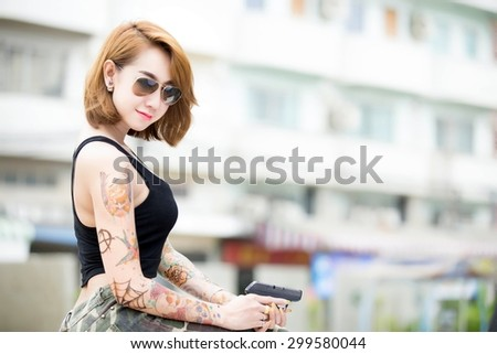 Beautiful Asian woman wearing glasses with a tattoo on the body. Caliber pistol in hand - stock photo