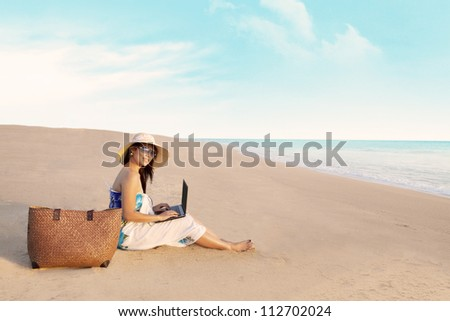 Beautiful asian woman with a bag working on laptop computer at beach - stock photo