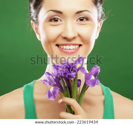 Beautiful asian woman with flower iris over green background - stock photo