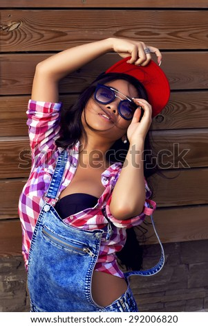 Beautiful asian woman with long curly hair in black cap, stylish sunglasses, checkered shirt and denim overalls poses on wooden background. Perfect clean skin. Full lips. Lifestyle. - stock photo
