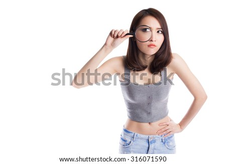Beautiful asian woman with magnifying glass - stock photo
