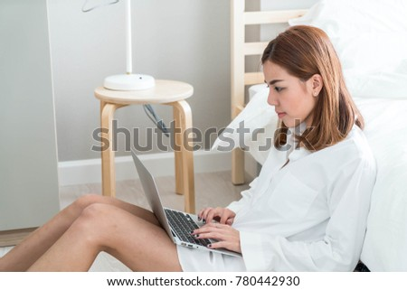 Beautiful asian woman working at home with laptop and telephone
