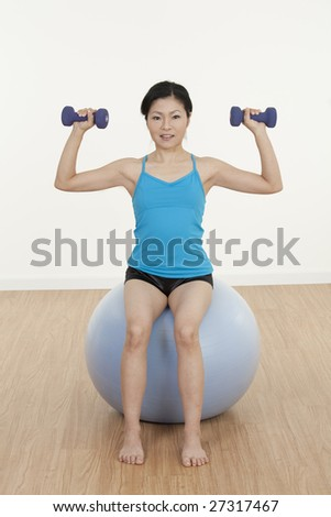 Beautiful Asian woman working out with fitness ball and dumbbells